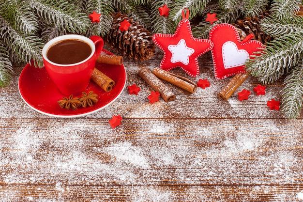 Transparent świąteczny z zielonym drzewem, szyszki, czerwony kubek z gorącą czekoladą, ręcznie robione ozdoby z filcu