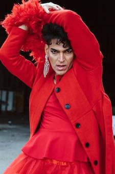 Transpłciowa kobieta w czerwonym ubraniu, pozująca, na tle ulicy. koncepcja lgtb i moda.