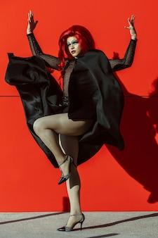 Transpłciowa kobieta w ruchu, patrząc w kamerę, na tle czerwonej ściany na ulicy.