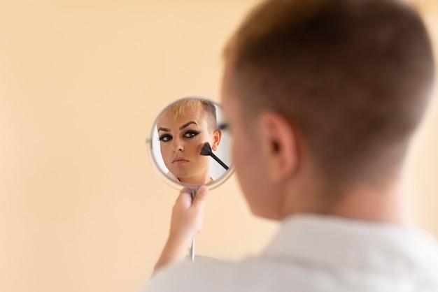 Transpłciowy nakładający makijaż z bliska