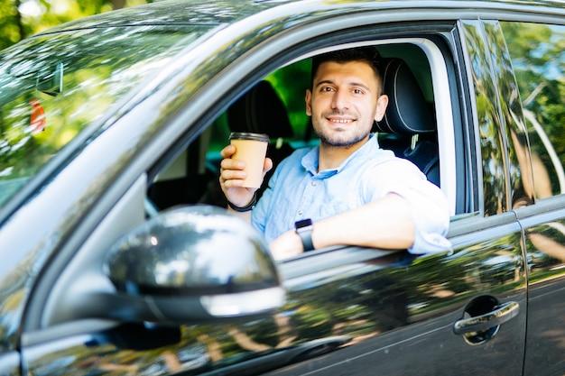 Transport i koncepcja pojazdu młody mężczyzna pije kawę podczas prowadzenia samochodu