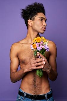 Transseksualny mężczyzna z kwiatami na fioletowym tle przystojny latynoski mężczyzna z bukietem seksowny wysportowany