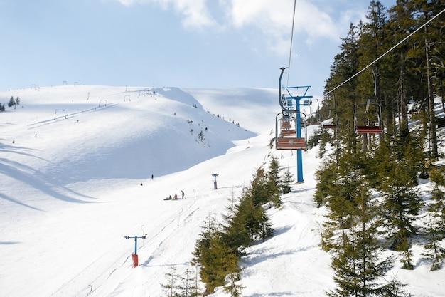 Trasa narciarska i wyciąg krzesełkowy z ośnieżonymi drzewami w słoneczny dzień. teren narciarski combloux, alpy francuskie