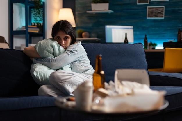 Traumatyczna rozczarowana sfrustrowana dwubiegunowa kobieta trzymająca poduszkę wyglądająca na zagubioną w aparacie