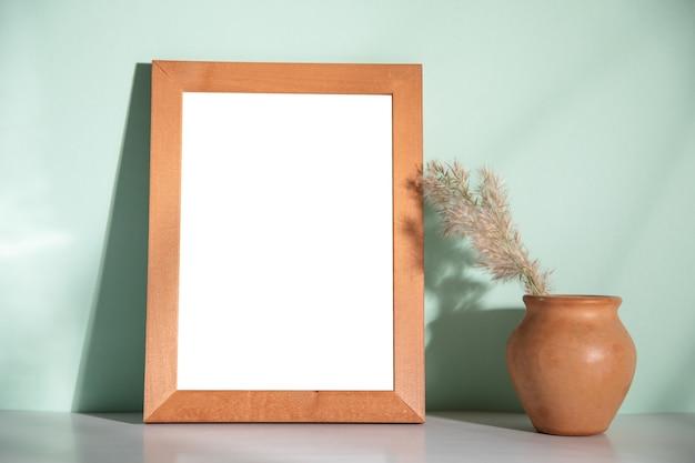 Trawa na glinie i ramka na zdjęcia na stole