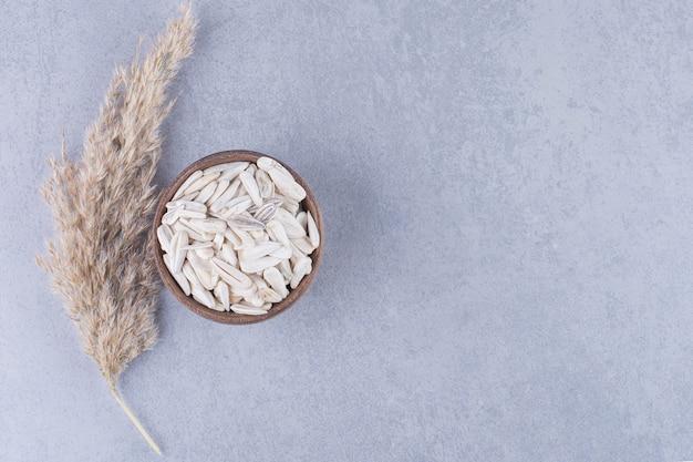 Trawa pampasowa i miska nasion słonecznika na marmurze.
