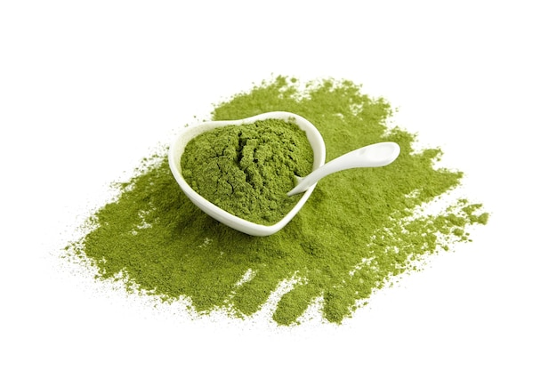 Trawa pszeniczna lub jęczmienna w proszku w ceramicznej misce i łyżka na białym tle. pożywienie detoksykacyjne