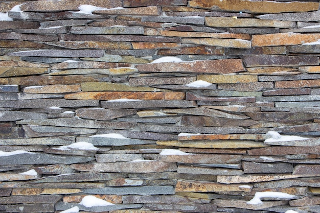 Trawertynowa faktura kamienia pokrywającego ściany domu.