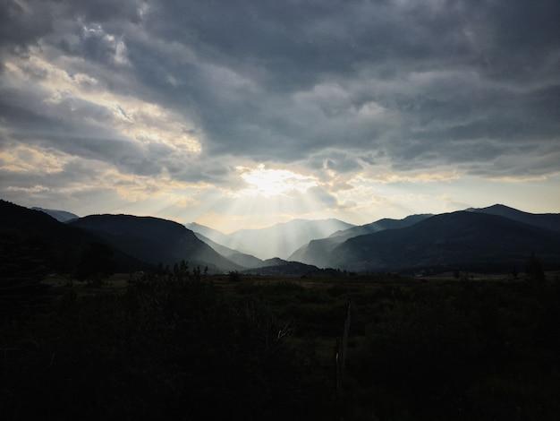 Trawiaste pole z roślinami z górami i słońcem świecącym przez chmury w tle
