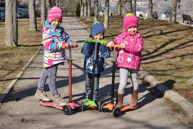 Treee dzieci na skuterach w parku