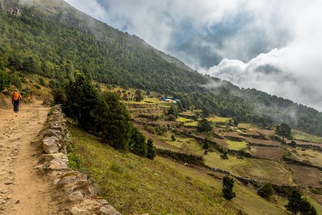 Trekker odprowadzenie w khumjung zieleni wiosce blisko namche bazaru w everest bazy obozowym regionie, nepal