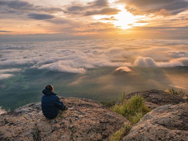 Trekker siedzi na górze z pięknym wschodem słońca i morzem mgły rano na górze khao luang w parku narodowym ramkhamhaeng w tajlandii, w prowincji sukhothai