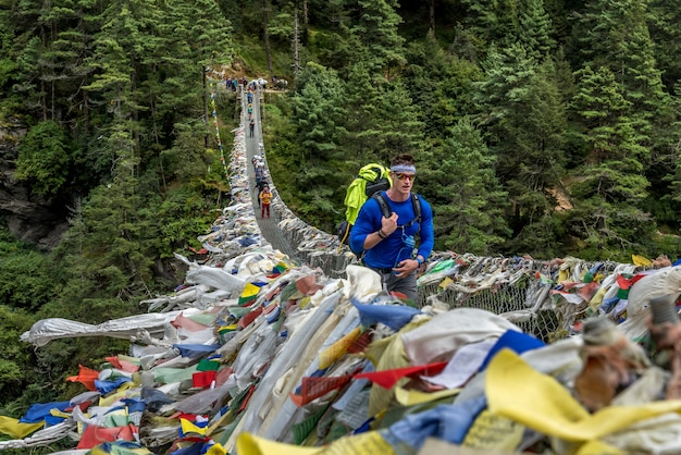 Trekkers krzyżuje zawieszenie most w everest regionie, nepal.