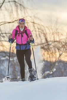 Trekking z dużą ilością śniegu w rakietach śnieżnych. samotna dziewczyna