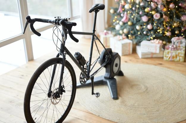 Trenażer rowerowy lub rower stacjonarny w pokoju z drewnianą podłogą i świątecznymi prezentami pod choinką