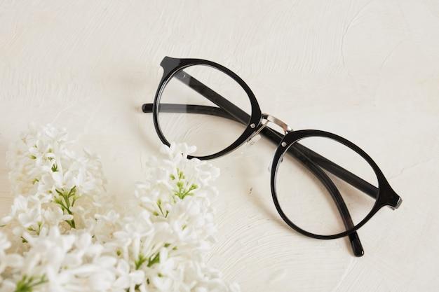 Trend w czarnych okularach i gałązka białego bzu na teksturowanym beżowym tle, okularach i kwiatach