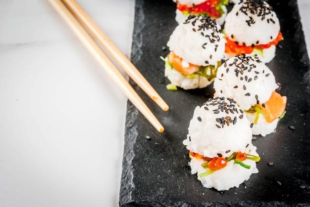 Trend żywności hybrydowej. japońska kuchnia azjatycka. mini sushiburgery, kanapki z łososiem, hayashi wakame, daikon, imbir, kawior czerwony. stół z białego marmuru, pałeczkami, sosem sojowym.