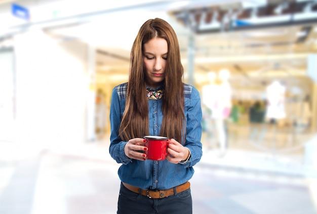Trendy młoda kobieta patrząc w czerwonym puchar