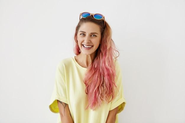 Trendy, moda i koncepcja nowoczesnego stylu życia. ładna nastolatka z przyjemnym uśmiechem i długimi krzaczastymi włosami