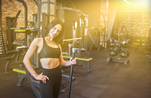 Trener aerobiku. wesoła młoda brunetka w sportowej, trzymając w ręku gimnastyczny pasek ciała i patrząc na kamery w siłowni