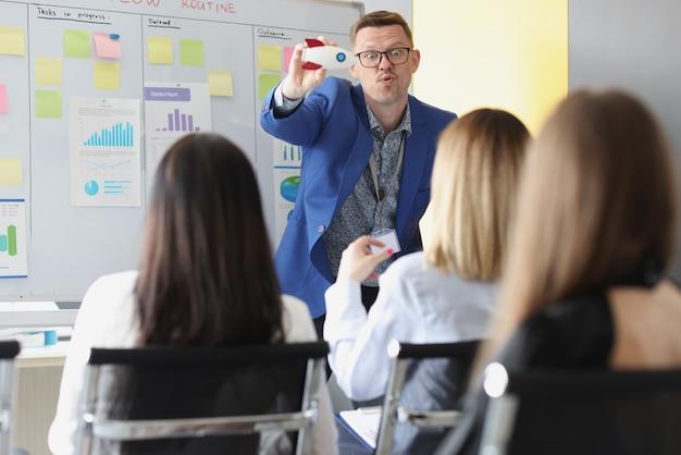 Trener biznesu w okularach pokazujący słuchaczom rakietę-zabawkę