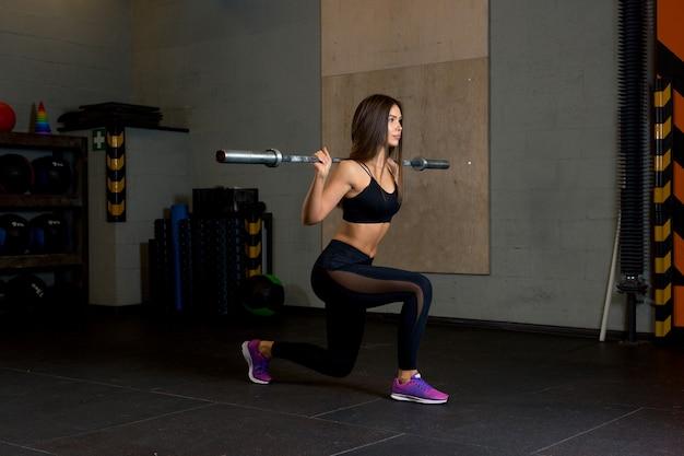 Trener fitness dziewczyna wykonuje wypady ze sztangą w siłowni pośród sprzętu sportowego.