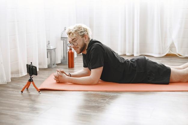 Trener fitness lub bloger wideo robi rozciąganie. mężczyzna filmuje się kamerą smartfona w domu.