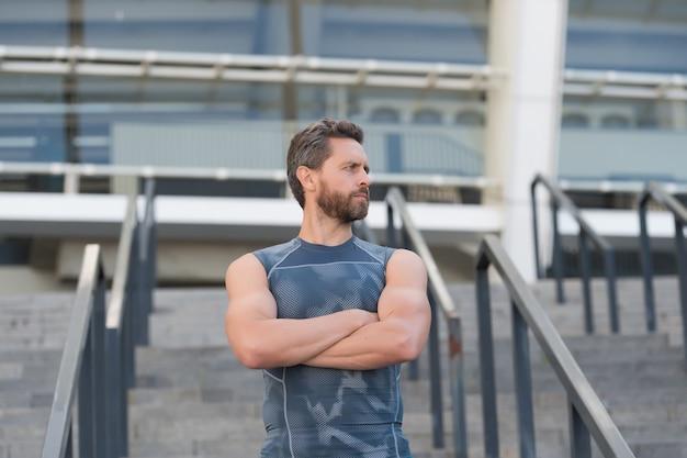 Trener fitness mięśni mężczyzna czeka na schody stadion wejście tło.