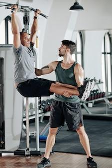Trener fitness mówi klientowi, aby trzymał się prosto, gdy wisi na drążku w siłowni i podnosi nogi
