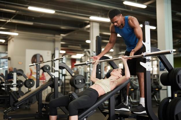 Trener fitness pomaga klientowi