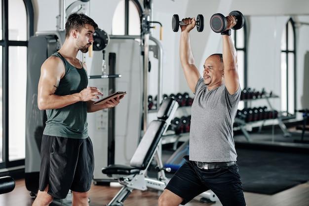 Trener fitness robienie notatek w dokumencie na komputerze typu tablet, gdy jego klient podnosi ręce z ciężkimi hantlami i robi rzuty