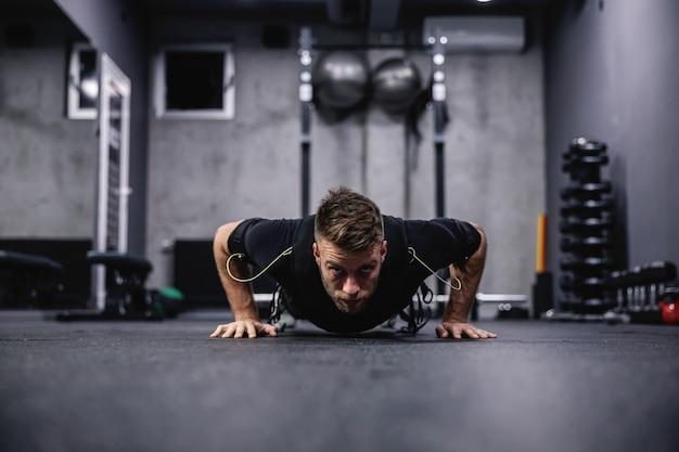 Trener fitness w specjalnym garniturze dla technologii ems, wykonujący ćwiczenia ramion i klatki piersiowej oraz pompki w nowoczesnej koncepcji siłowni. rewolucja w treningu, rehabilitacji ciała