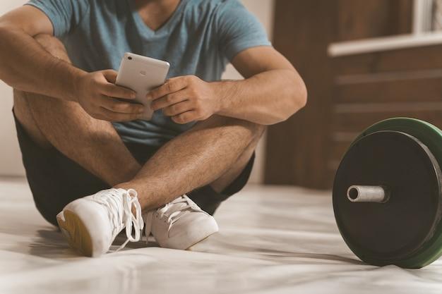 Trener fitness, wyszukiwanie online, siedząc na podłodze ze smartfonem