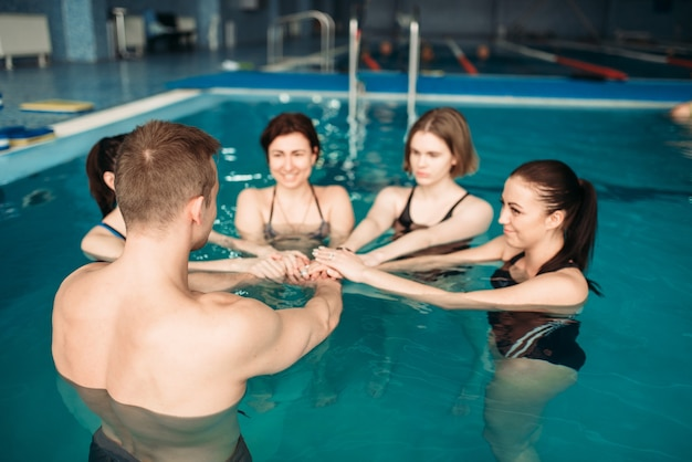 Trener i grupa kobiet na zajęciach aqua aerobiku na basenie. trening fitness w wodzie, zdrowy tryb życia