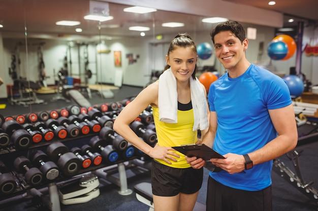 Trener i klient omawiają jej postępy na siłowni