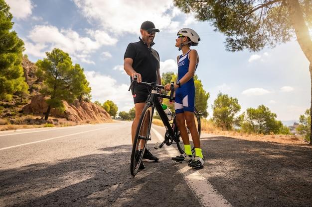 Trener i ojciec rozmawiają ze swoim uczniem i synem na drodze o jeździe na rowerze