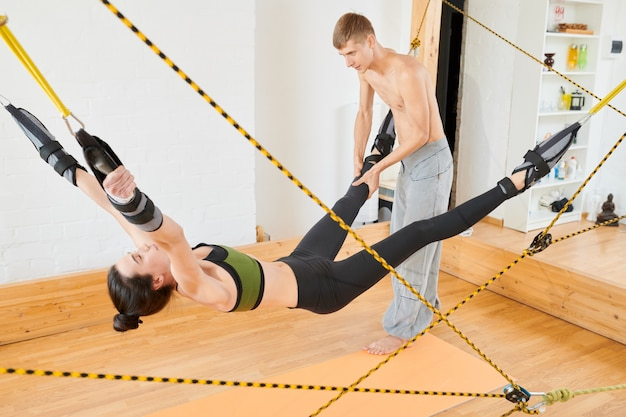 Trener jogi, rozciąganie nogi kobiety na huśtawce jogi