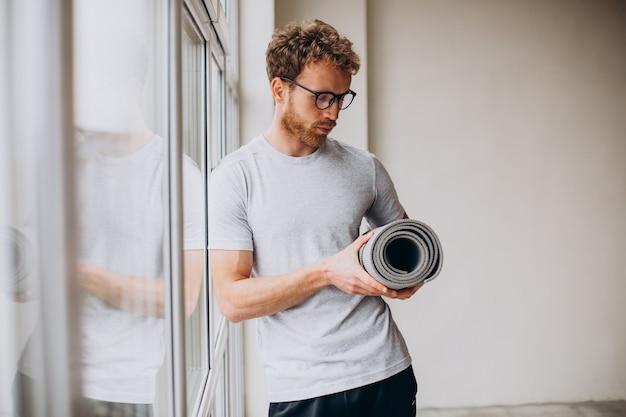 Trener jogi stojący z matą przy oknie