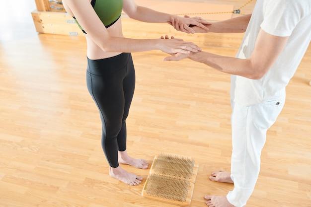 Trener jogi wspierający kobietę, gdy będzie stać na paznokciach