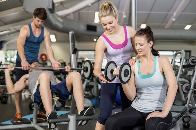Trener kobieta pomaga kobieta podnoszenia hantle w siłowni