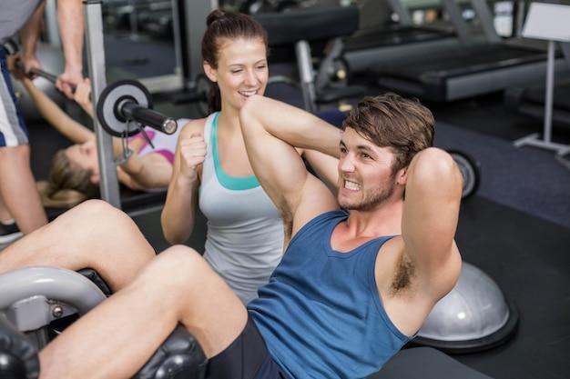 Trener kobieta pomaga mężczyzna robi jego brzuszki na siłowni
