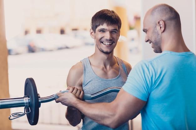 Trener kontroluje ćwiczenia fizyczne mężczyzny