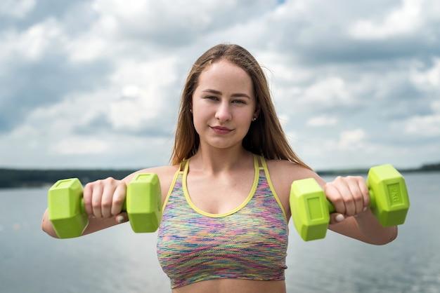 Trener lekkoatletycznego fitness młodych ćwiczeń z hantlami na plaży nad jeziorem. zdrowy tryb życia
