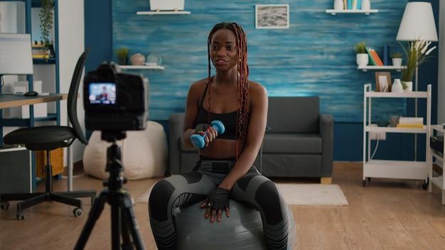 Trener lekkoatletycznego kobieta rozciąganie mięśni ciała nagrywania porannego treningu jogi z hantlami w salonie. slim fit dorosły ubrany w sportową filmowanie samouczek gimnastyczny siedzący na szwajcarskiej piłce