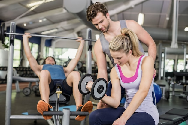 Trener mężczyzna pomaga kobieta podnoszenia hantle w siłowni