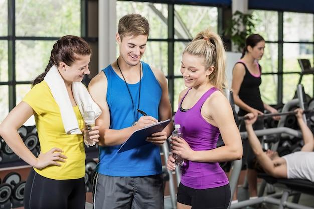 Trener mężczyzna rozmawia z sportswomen na siłowni