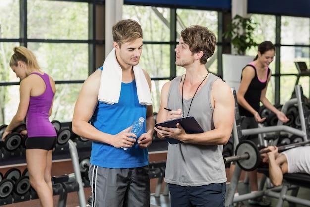 Trener mężczyzna rozmawia ze sportowcem w siłowni