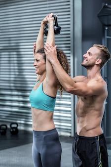 Trener mięśni pokazuje, jak podnosić kettlebells