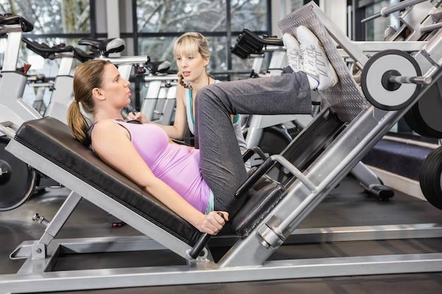 Trener motywujący kobiety w ciąży podczas korzystania z prasy nóg na siłowni