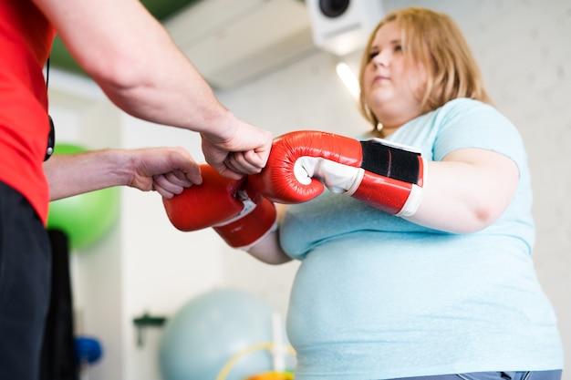 Trener motywujący otyłą kobietę